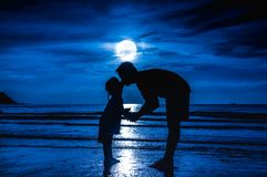 Father`s day. Silhouette side view of loving child kissing her f. Ather. Family enjoying and relaxing on beach with full moon on blue sky background in the Royalty Free Stock Images