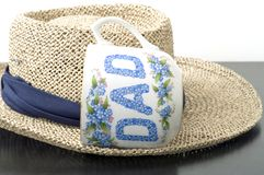 Father's day tea cup on hat. Blue and white father's day collectible tea cup or coffee cup mug sitting sideways on a light tan color colour woven rattan stock photos