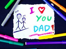 Father`s day theme with I LOVE YOU DADD message. Kid drawing of father holding his child for happy father`s day theme with I LOVE YOU DADD message Royalty Free Stock Photography