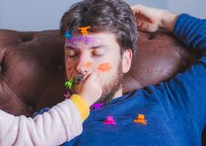 Free Father`s Day. Young Man Sleeping While His Little Daughter Paints His Face Royalty Free Stock Photo - 174795555