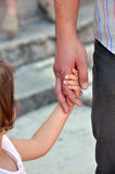Father's hand holding a child's hand, closeup. Image showing father guiding a child Royalty Free Stock Photo