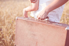 Father's hand holding a retro suitcase and a Stock Photos