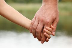 Father`s hand lead his child son against summer forest and river. Nature outdoor background, trust family concept royalty free stock photography