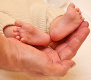 Father's hands cradling his infant son's feet Royalty Free Stock Image