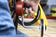 Father`s hands that installs additional wheels on the sides of the new children`s bicycle, for the safe riding of the child. Close-up royalty free stock photo