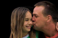 A Father's Kiss. A father kissing his daughter on the cheek stock images