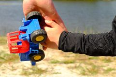 Father's large hand pass plastic toy truck to hand of a little boy. Hands in blue and black shirts. Royalty Free Stock Images