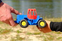 Father's large hand pass plastic toy truck to hand of a little boy. Hands in blue and black shirts. Royalty Free Stock Photos