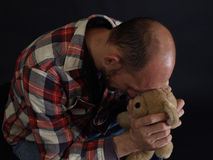 Father's Loss. An older balding male grips a teddy bear, head bowed down Stock Photos