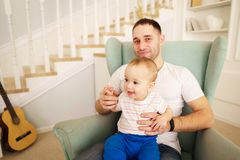 Father`s love, family value, loving relationship. Father`s love, family value,  loving relationship. daddy`s little boy. men holding little son on laps. young stock photo