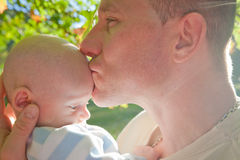 Father's Love. A father holding his young son outside kissing him on the forehead. The image is horizontal Royalty Free Stock Images