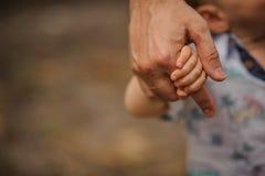 Father& x27; s ręki prowadzenie jego dziecko syn w lato lasowej naturze plenerowej, fotografia stock