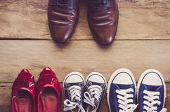 Father`s shoes Placed in front of mother`s shoes with baby on wo. Oden floor - Concept of family leader Stock Images