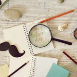 Father`s tools, black paper mustache, magnifying glass, pencils and a greeting inscription in a notebook on a light wooden table. Top view, father`s day royalty free stock photos