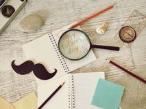 Father`s tools, black paper mustache, magnifying glass, pencils and a greeting inscription in a notebook on a light wooden table. Compass, fatherly tools, black stock photography