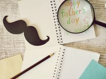 Father`s tools, black paper mustache, magnifying glass, pencils and a greeting inscription in a notebook on a light wooden table. Top view, father`s day stock image