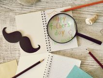 Father`s tools, black paper mustache, magnifying glass, pencils and a greeting inscription in a notebook on a light wooden table. Top view, father`s day royalty free stock photography