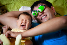 Father scares his daughter. And she cries. Asian family royalty free stock photos