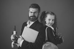 Father and schoolgirl with proud and happy faces on terracotta. Background. Family and home schooling concept. Girl and men in suit and school uniform. Kid and stock photos