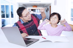 Father scolding his daughter to study. Portrait of young father scolding his female child for doing homework at home Stock Photography