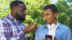 Father scolding young son phone showing marijuana weed, bad habits prevention