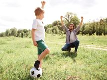 Father is screaming and yelling. He is very happy for his son. Boy played a good game. He won. Boy is standing besides. His father and holding ball with leg Royalty Free Stock Images
