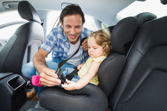 Father securing baby in the car seat Royalty Free Stock Photo