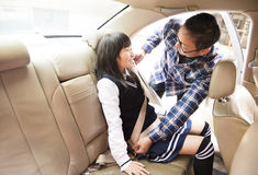 Father securing daughter in the car seat Royalty Free Stock Photos