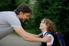 The father sees off the son-schoolboy in school. Royalty Free Stock Photography