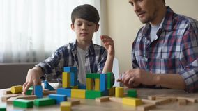 Father and serious son playing with toy cubes, building house together, leisure