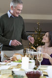 A father serving Christmas dinner to his daughter Stock Photography