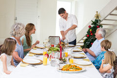 Father serving Christmas meal to family. At dining table Stock Photography