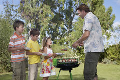 Father Serving Grilled Food To Kids Outdoors. Side view of father serving grilled food to children in the garden Royalty Free Stock Photos