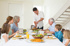 Father serving meal to family. At dining table Royalty Free Stock Images