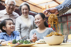 Father serving noodles with chopsticks at a family dinner royalty free stock image