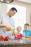 Father serving orange juice for children in kitchen Royalty Free Stock Photos