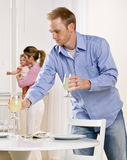 Father setting table as mother holds baby daughter royalty free stock image