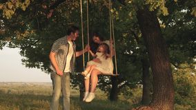 Father shakes mother and child on a rope swing on an oak branch in forest. Mom shakes her daughter on swing under a tree stock video