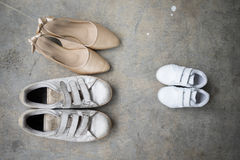 Father shoes, son shoes and mother gold high heel shoes. On cement background, family concept Stock Photo