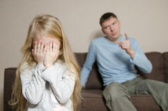 Father Shouting At Young Daughter. Girl is closing eyes with her hands Stock Photos