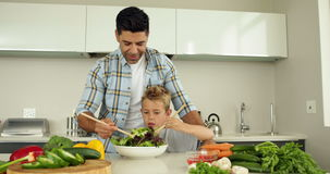Father showing his son how to toss a salad