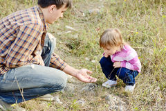 Father showing little lizard to daughter Stock Photography