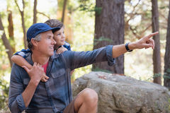 Father showing something to curious boy. While hiking in forest royalty free stock photo