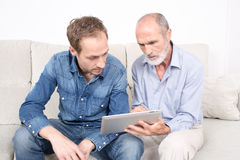 Father showing something to his elderly son. Father and son looking at ipad device Royalty Free Stock Photos