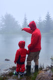 Father showing something to son on lake Stock Photo