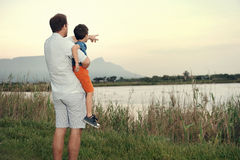 Father showing son. Father pointing out something to son at sunset while holding him in arms Royalty Free Stock Image
