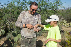 Father shows the child a rare lizard - Gila monster Royalty Free Stock Photos
