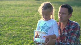 Father shows his daughter how to control drone stock video footage