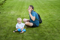 Father shows his son how to blow soap bubbles Royalty Free Stock Photo