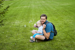 Father shows his son how to blow soap bubbles Stock Images